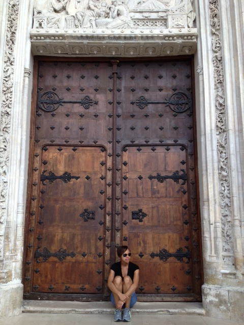 Girl sitting in front of door of cathedral in Madrid, Spain