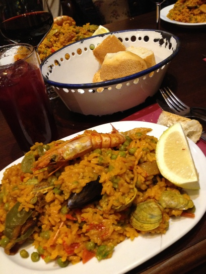 a plate of paella and a glass of sangria